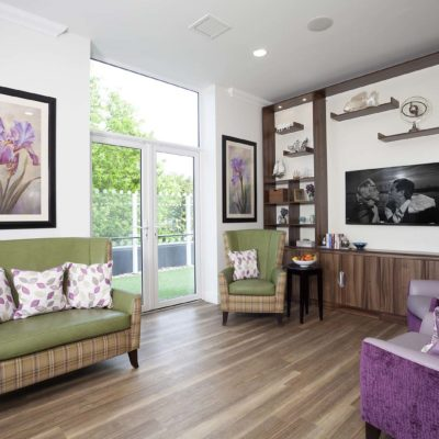 Living room with green and purple chairs at Oaklands Care Centre Southampton